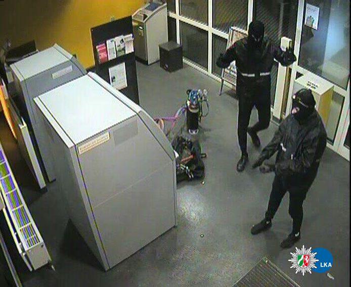 Twee verdachten vanmorgen in actie bij de bank, vlak voor hun arrestatie.