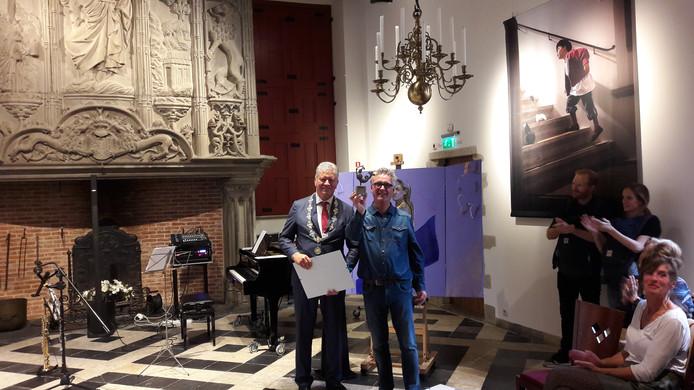 Kunstenaar Mart Franken toont de replica van de zeeridderwindvaan die bij de Sakkoprijs hoort. Links burgemeester Frank Petter