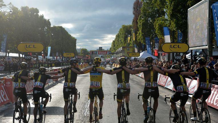 Chris Froome (geel, m) komt met zijn team Sky over de finish in Parijs in 2015 Beeld a