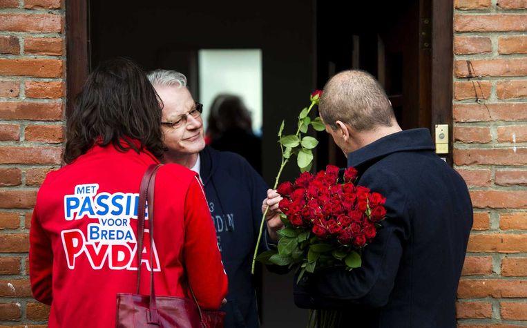 PvdA-fractievoorzitter Diederik Samson en Miriam Haagh, lijsttrekker van de partij in Breda, gaan samen met rozen de deuren langs in Breda. Beeld anp