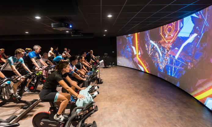 Een spinning-training in de nieuwe fietshal Cycle Dome, met bioscoopscherm.