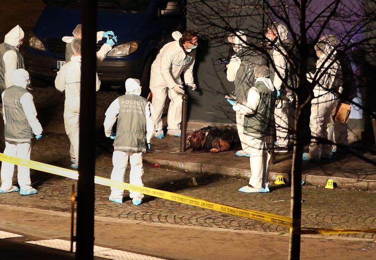 Een politieauto rijdt de schutters tegemoet bij Charlie Hebdo. Hierboven: het lichaam van de doodgeschoten Coulibaly. Beeld EPA