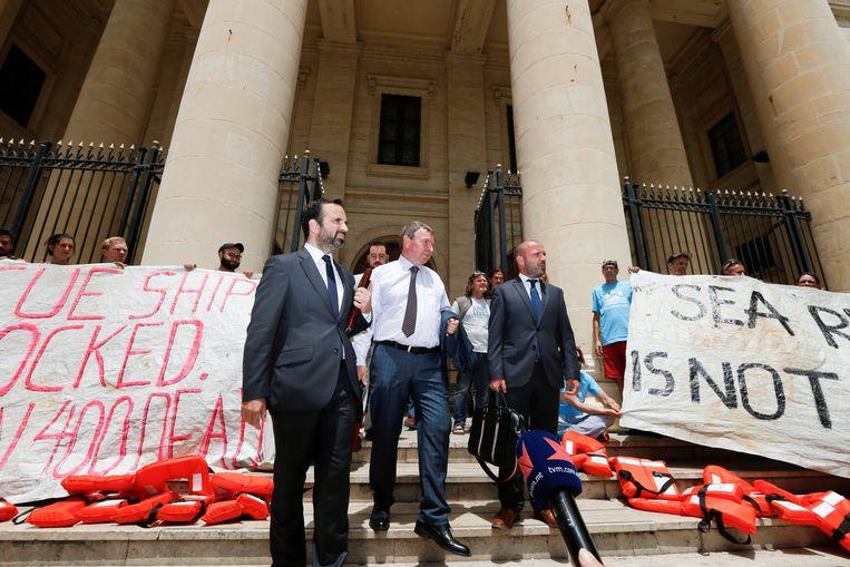 Claus-Peter Reisch (midden), de kapitein van Lifeline, verlaat de rechtbank.