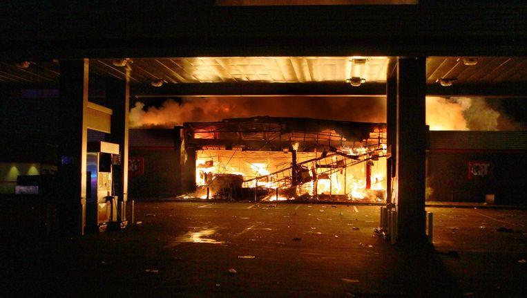 Een winkel in Ferguson brandt nadat deze in brand was gestoken door relschoppers Beeld ap