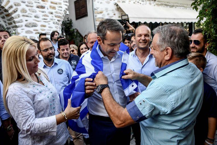Leider Kyriakos Mitsotakis (midden) van de rechts-conservatieve partij Nieuwe Democratie op campagne.  Beeld AFP