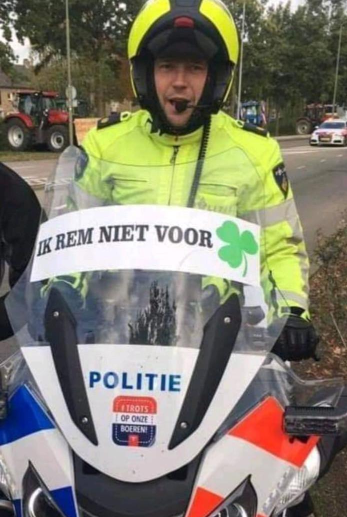 De agent met de bewuste sticker op het windscherm van zijn motor.