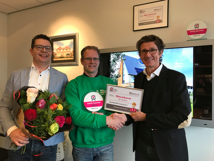 Edwin Groot van bouwnu.nl (r) feliciteert Martijn Blankenvoorde van Bouwbedrijf Vosman uit Raalte. Links Vosman-directeur Remco Harink