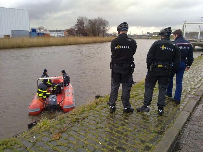 Politie- en brandweermensen zoeken in het water langs de Nieuwe Prinsenkade en Markkade naar de vermiste Bredanaar Youri Bicker.foto Leo Nierse