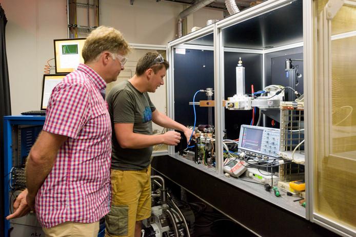 Onderzoeker Gerard van Rooij (l) van Differ bekijkt in het laboratorium het werk van een medewerker.