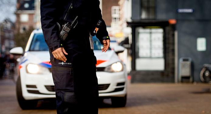 2015-01-22 12:54:29 GRONINGEN ILLUSTRATIE - Een politieagent op straat. Agent, politie, politieauto, politiewagen, dienstwagen, dienstauto. ANP XTRA KOEN VAN WEEL