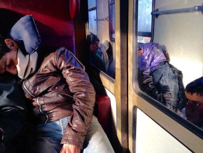 Uitgeputte vluchtelingen in de trein in Macedonië.