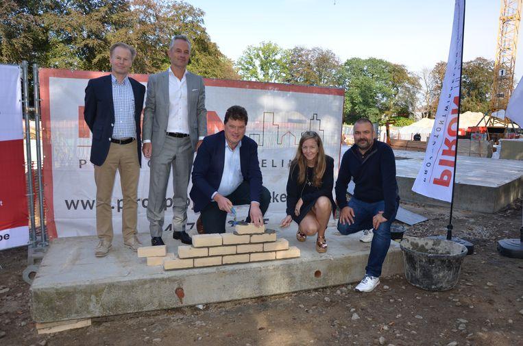 Dirk D'haese, David Piron, burgemeester Filip Anthuenis, gedeputeerde Hilde Bruggeman en Open Vld-voorzitter Stefan Walgraeve leggen samen de eerste steen van het seniorencomplex.