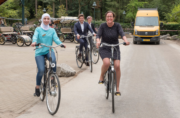 Elham uit Syrië en staatssecretaris Tamara van Ark (rechts) fietsen over het terrein van  Center Parcs Het Heijderbos.
