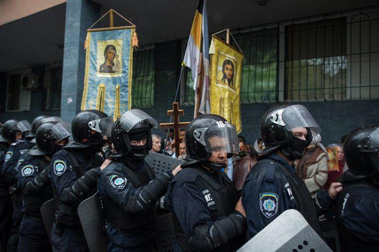Oekraïense agenten bewaken het politiebureau in Odessa waar demonstranten proberen pro-Russische arrestanten te bevrijden Beeld EPA