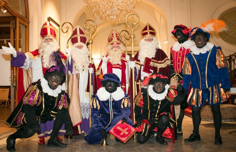 De man die Sinterklaas bijstaat in Sint-Niklaas (centraal), samen met de 'cursisten' van de opleiding 'De Goede Sint' van het Sint-Nicolaasgenootschap.