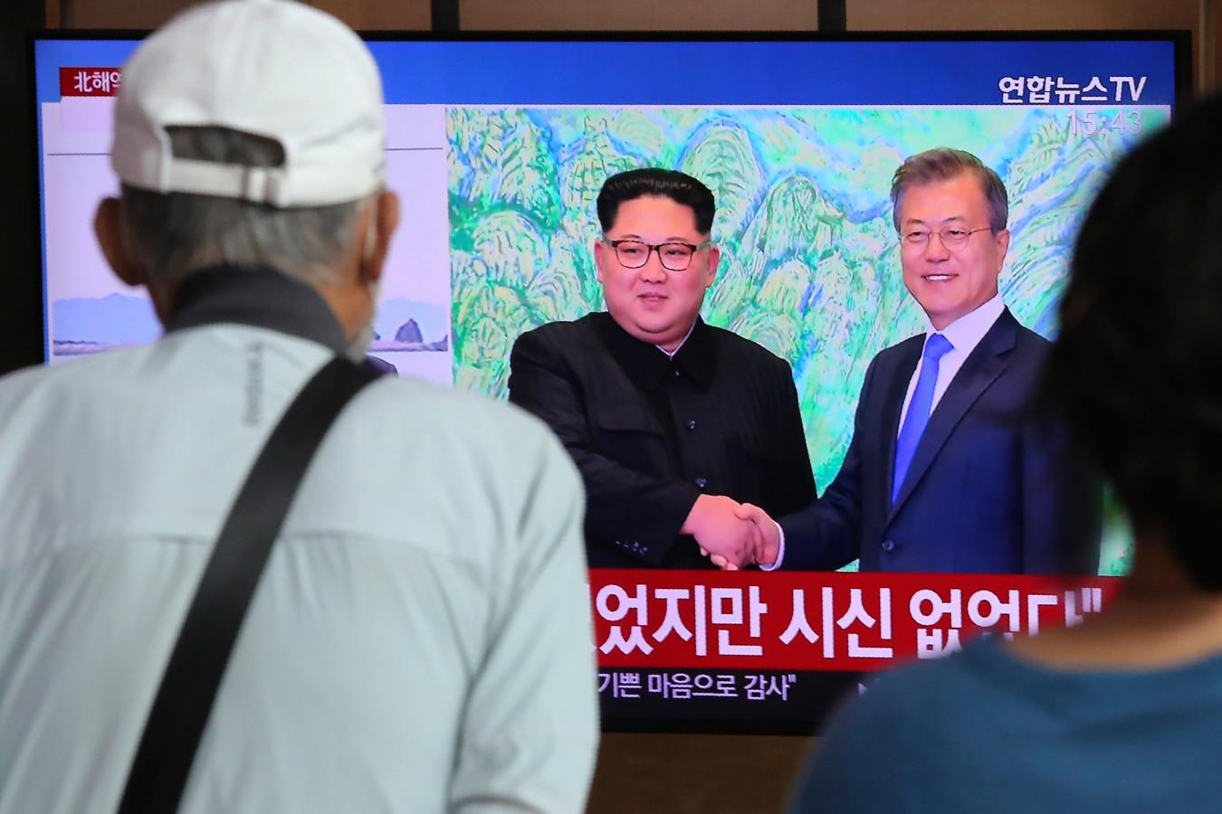 Reizigers op een station in Seoel kijken naar archiefbeelden van de presidenten Kim Jong-un (links) en Moon Jae-in.