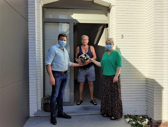 Schepen Tom Braet bedankt samen met een vrijwilliger een van de mantelzorgers.