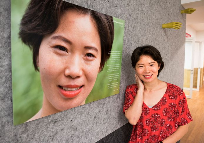 Lili Chang bij haar levensgrote portret in de bibliotheek aan de Neude, waar een foto-expositie is ingericht, gewijd aan Utrechters met een migratieachtergrond.