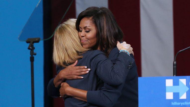 Michelle Obama omhelst Hillary Clinton na haar toespraak op een verkiezingsbijeenkomst in New Hampshire. Beeld photo_news