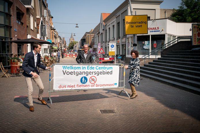 Jan-Pieter van der Schans (links), Ernst Steinmeijer en Sara Kakebeen plaatsen het hek op het Maandereind.