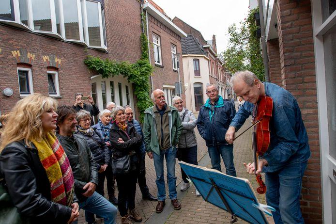 Violist Jan-Willem Vis geeft een concertje aan zijn voordeur in het Tilburgs dwaalgebied.