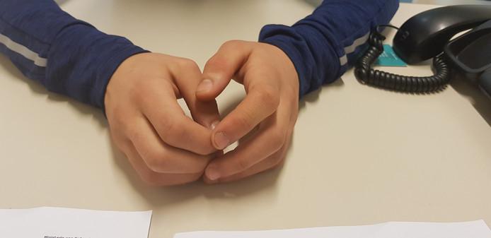 De handen van de 12-jarige jongen, tijdens zijn gesprek met zijn advocaat.