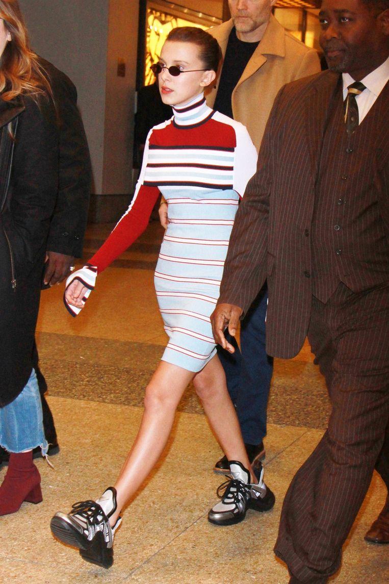 Millie in een jurk en sneakers van Louis Vuitton.