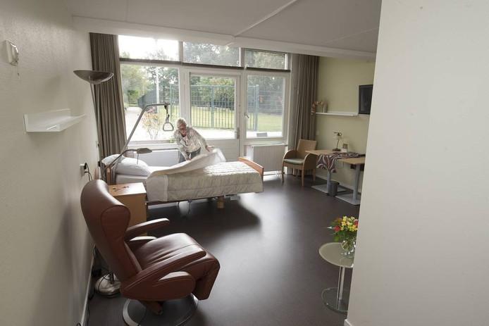 Een vrijwilligster maakt een van de gastenkamers in een hospice in gereedheid. Foto Theo Kock