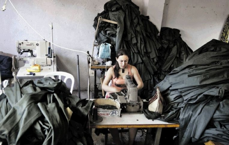 Een naaister in Albanië zet uniformen voor het Griekse leger in elkaar. (FOTO REUTERS) Beeld REUTERS