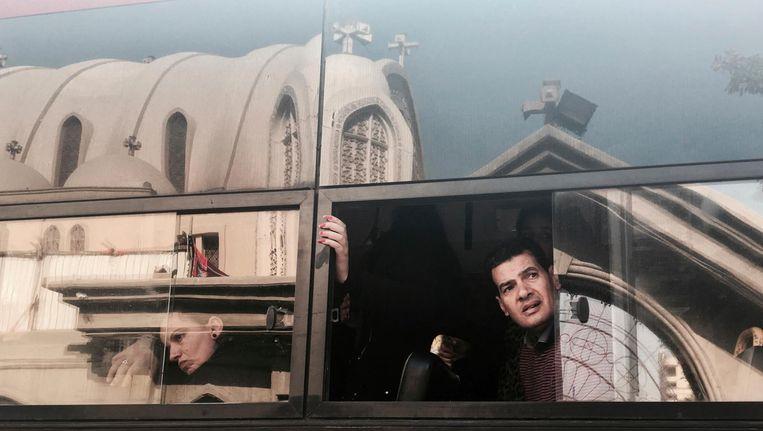 Nabestaanden van slachtoffers van de aanslag op de kathedraal in Cairo verlaten maandag per bus de begrafenisdienst. Beeld AP
