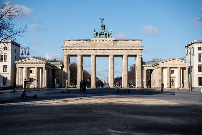 Duitse politieagenten  op het vrijwel verlaten plein voor de Brandenburger Tor, waar het in het weekend normaliter krioelt van de selfiesmakende bezoekers.