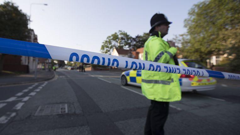 Een straat is afgezet in Wigan waar de politie een huiszoeking uitvoert. Beeld afp