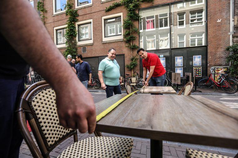 Personeel van pizzarestaurant Il Primo in de Reguliersdwarsstraat meet precies uit waar de terrastafels mogen staan Beeld Eva Plevier