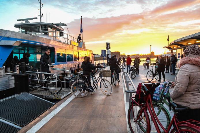 Fietsers wachten aan de Merwekade op de Waterbus om vervolgens naar Papendrecht te gaan.
