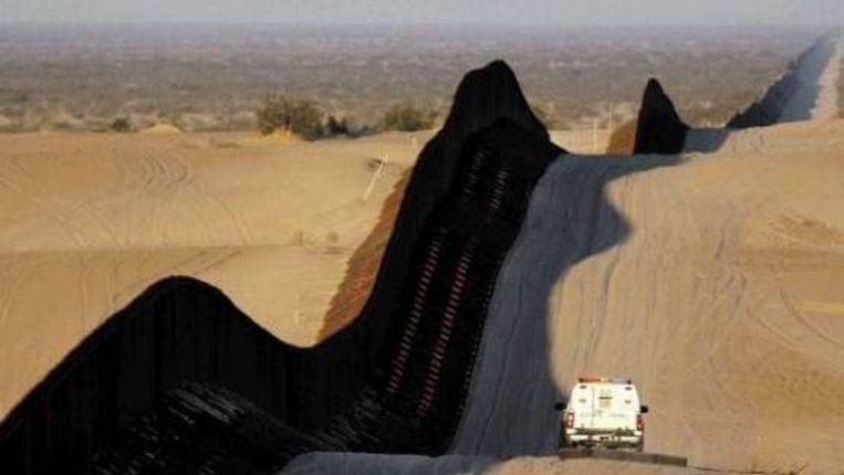 Een wagen maakt langs de grens met een sleep van autobanden het zand weer glad, zodat sporen van illegalen beter zichtbaar zijn. (FOTO AFP) Beeld