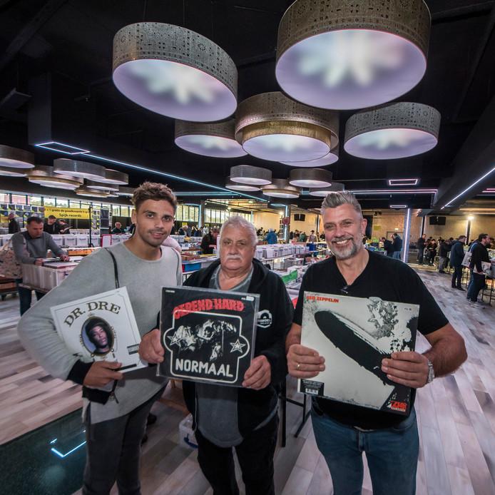 Vinyl is weer in trek. Bij de platenbeurs in de Expo Hal in Enschede laten liefhebbers hun favoriete album zien. Van rechts naar  links organisator Wilco de Bruin, met Led Zeppelin, zijn vader Willem (Normaal) en zijn zoon Dylan (dr. Dre). Foto Reinier van Willigen