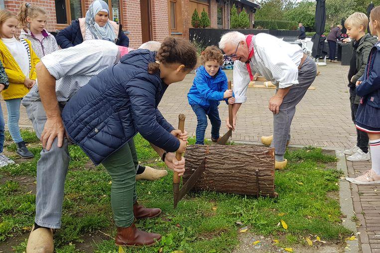 Eric De Keyzer toont jongeren hoe vroeger klompen werden gemaakt uit stukken boom.
