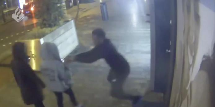 Een jonge man grist de smartphone van een van de vrouwen uit haar hand.