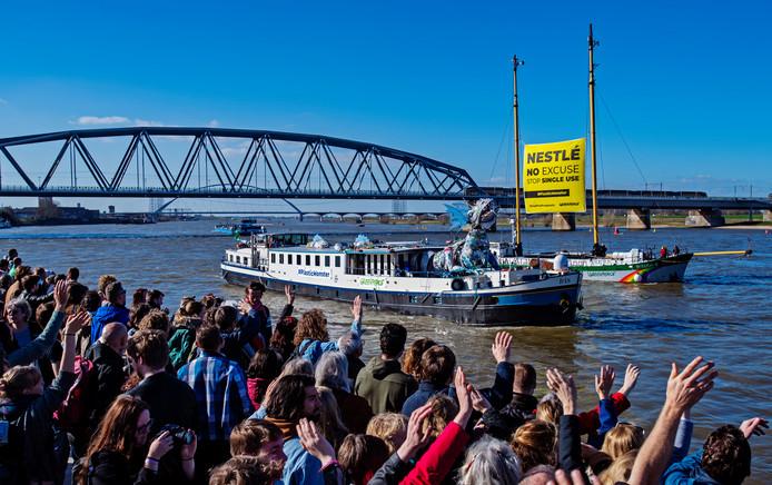 Bezoekers van het Plastival op de Waalkade in Nijmegen zwaaien het schip met het 'plasticmonster' uit dat op weg gaat naar Nestlé in Zwitserland.