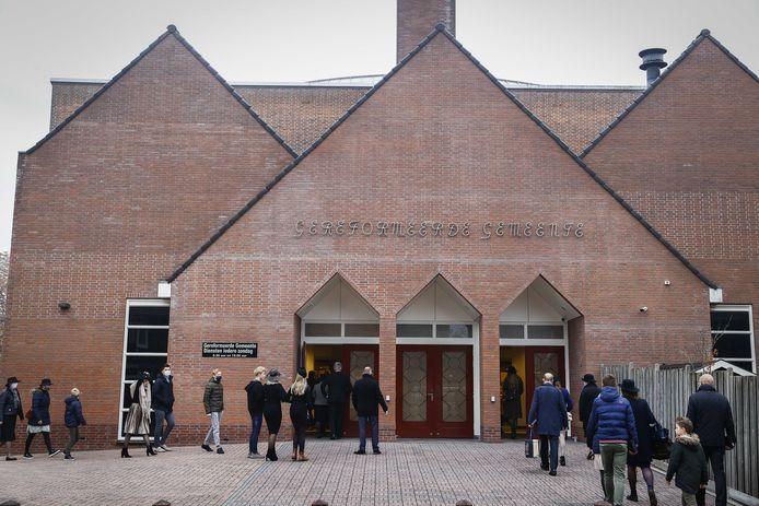 Kerkgangers komen aan bij de Rehobothkerk in Barneveld voor de wekelijkse kerkdienst.