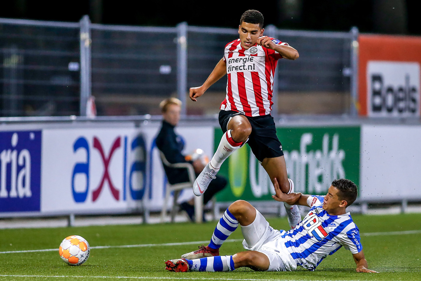 Jay Idzes zet een tackle in,  Zakaria Aboukhlal van Jong PSV ontwijkt.