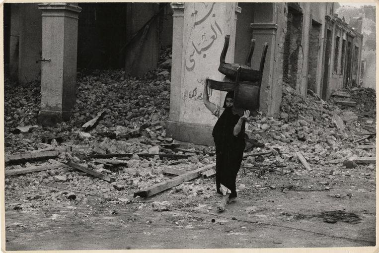 Vrouw loopt door het puin met een stoel op haar hoofd, Port Said, Egypte, november 1956. Beeld Chim (David Seymour) / Magnum Photos Courtesy Chim Estate