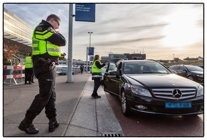 Inspecteurs van de ILT houden een illegale taxi aan op Schiphol, samen met het politieteam Dienst Infra Amsterdam