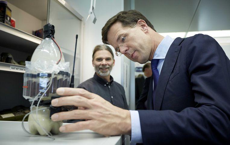 Een explosievenexpert van het Nederlands Forensisch Instituut (NFI) laat minister-president Mark Rutte een geïmproviseerde bom zien. Beeld ANP