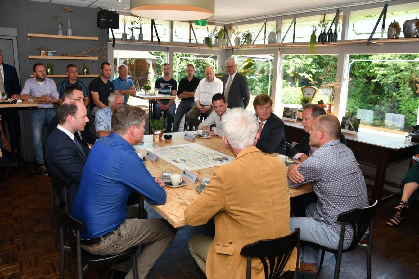 Koning Willem-Alexander met vrijwilligers van energiecoöperatie Hilverstroom.