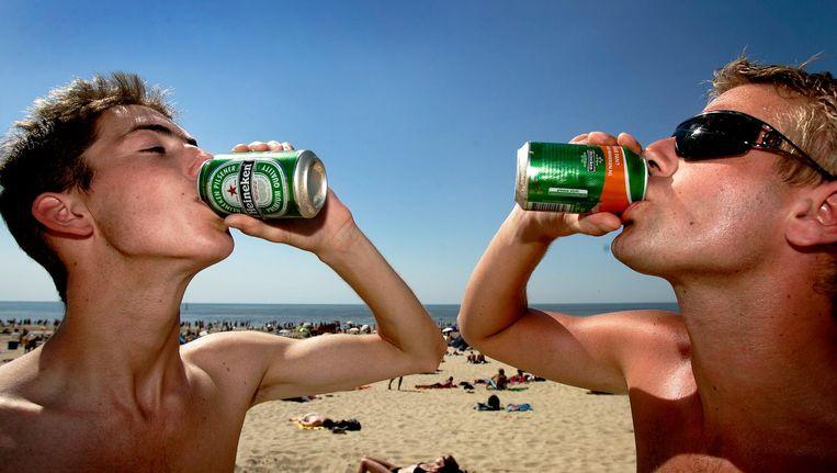 Hoofdpijn of geen hoofdpijn? Deze strandgasten in Egmond aan Zee lessen de dorst met een biertje. Beeld anp