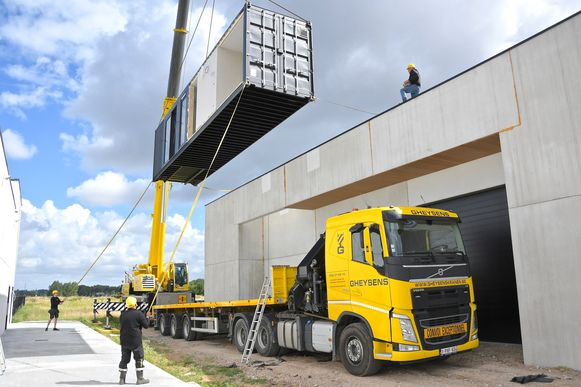 Als eerste werd de 12 meter lange container op het dak van de loods gehesen.