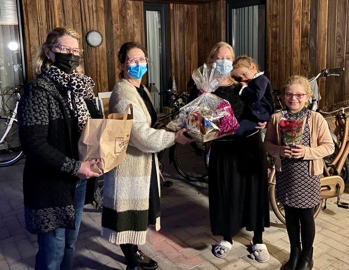 Els (links) en Marijke (midden) van 'graag gedaan' overhandigen het kerstpakket aan Sofie Engelen en haar twee dochtertjes