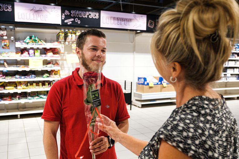 Antonio krijgt voor z'n inzet bij Carrefour Genk een rode roos van Carine Meuwis, voorzitter van de socialitistische vakbond BBTK Limburg.