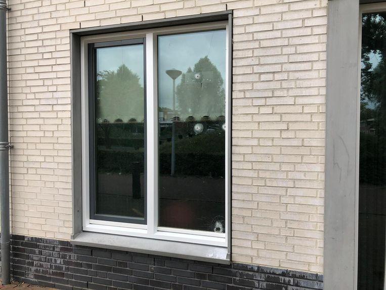 In het raam zijn zaterdagochtend nog meerdere kogelgaten te zien. Beeld Het Parool